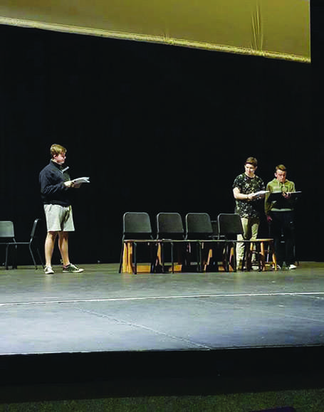 Senior Josh Allinson, junior Jakob Cody, and senior Nathaniel Gaswint learn the blocking on the stage during the rehearsal.