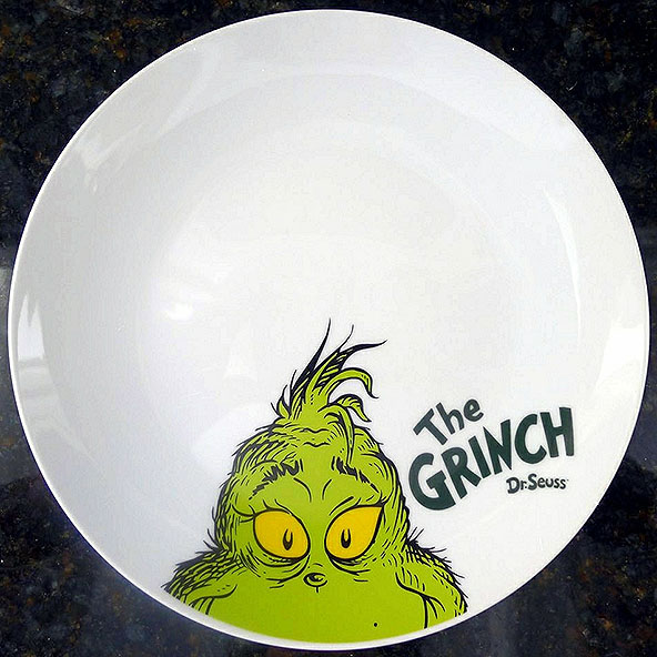"Give a Grinch a Break! The Grinch smiles up hopefully from a novelty dinner plate, imploring all those who see him to reconsider the anti-Grinch sentiment which runs rampant in this day and age. The term ""Grinch"" was first introduced by the legendary Dr. Seuss in 1955 and since then had been used liberally to refer to anyone who is less than jolly during the holiday season. ""I think it was two years ago I was called ""the Grinch"" because I refused to get up early for [Christmas],"" junior Journey Scott said."