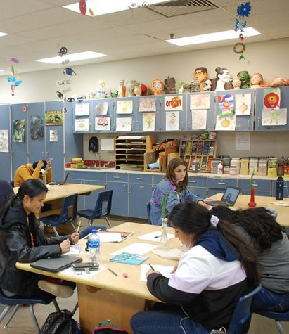 Senior Ruby Peterson, Cambyll Luxmore and their tablemates work hard and finish up their art pieces in art class.