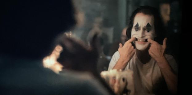 Joaquin+Phoenix+as+Arthur+Fleck+in+Joker.+Phoenix+is+in+character+as+the+Joker+in+a+scene+where+he+prepares+to+do+his+day+job+being+a+clown.